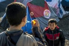 Iker Pastor, marzo 2016.  Due bambini giocano con le bolle di sapone sulla strada di un campo profughi a Idomeni, Grecia