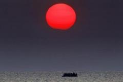 Yannis Behrakis (Reuters) 11 agosto 2015. Un gommone al tramonto pieno di profughi siriani alla deriva nelle acque del Mar Egeo, tra Grecia e Turchia, dopo un'avaria al motore al largo dell'isola di Kos