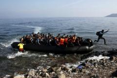 Yannis Behrakis (Reuters). 19 ottobre 2015. Un migrante afghano tocca terra saltando da un gommone pieno di profughi sull'isola di Lesbo